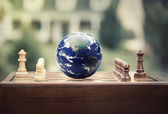 Chess game figures earth globe isolated on home background — Stock Photo