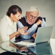 Woman teaching confused elderly man how to use laptop — Stock Photo #70158699