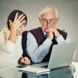 Woman teaching confused elderly man how to use laptop — Stock Photo #70158777