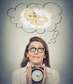 Woman anticipating a baby looking up holding alarm clock — Stock Photo