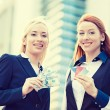 Happy business women holding credit cards and cash reward — Stock Photo #71115239