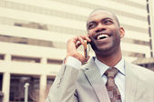 Handsome happy laughing young businessman talking on mobile phone  — Stock Photo