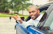 Happy, smiling, young man sitting in his new car showing keys — Stock Photo