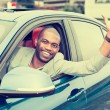 Happy young man driver stuck his hand out of the car window — Stock Photo #78206306