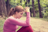Portrait stressed sad young woman sitting outdoors on summer day in park — Stock Photo