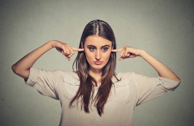 Angry unhappy woman with closed ears looking away