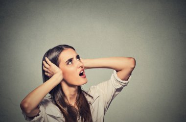 Annoyed stressed woman covering her ears, looking up loud noise upstairs