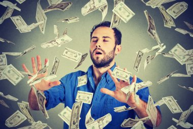 Business man with eyes closed trying to catch dollar bills flying in air walking through money rain