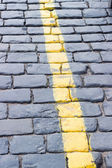 The yellow line on the road receding the stone — Stock Photo