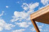 Canto de madeira contra o céu azul — Fotografia Stock
