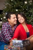 Jonge Spaanse koppel door de kerstboom — Stockfoto