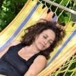 Mature woman relaxes on a hammock. — Stock Photo #62515811