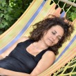 Mature woman relaxes on a hammock. — Stock Photo #64298633