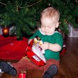Little baby biy sits under decorated Christmas tree — Stock Photo #61329351