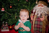 Little baby biy sits under decorated Christmas tree with Santa — Stock Photo