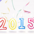 Burning candles with number 2015 and streamers flying on white b — Stock Photo #58524335