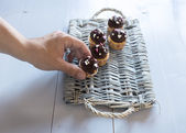 Hand putting a delicious chocolate cupcakes on a wicker tray — Foto Stock