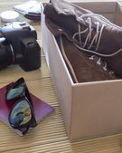 Open box with a pair of boots and camera. Man preparing to an adventure trip — Stock Photo