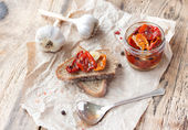 Fresh bread with sun-dried tomatoes on a wooden table. — Stock Photo
