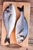 Two fresh gilt-head bream fish on cutting board — Photo