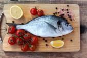 Two fresh gilt-head bream fish on cutting board — Stock Photo