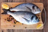Two fresh gilt-head bream fish on cutting board — Stock Photo