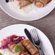 Grilled bavarian sausages with rice and mint on white dish — Stock Photo #54570409
