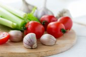 Cutting board with fresh vegetables on white wooden table — Stock Photo