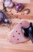 Raw pork schnitzel with meat tenderizer on wooden board — Stock Photo