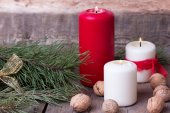 Burning candle with walnuts pine branches on wooden background — Stock Photo
