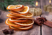 Sliced of dried orange, cinnamon sticks, anise stars and candle with pine brunch — Stock Photo