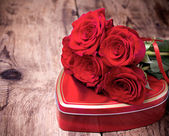 Gift box and bouquet of roses on wooden background. — Stock Photo