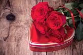 Συσκευασία δώρου και ανθοδέσμη με τριαντάφυλλα σε ξύλινα φόντο. — Φωτογραφία Αρχείου