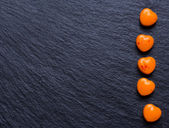 Orange heart shaped pills or candy on grunge black slate background. Copy space. — Stock Photo
