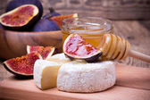 Camembert cheese with honey and figs on a wooden board. — Zdjęcie stockowe