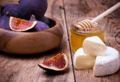 Camembert cheese with honey and figs on a wooden board. — Stock Photo