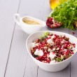 Healthy salad with pomegranate seeds, almond, feta cheese and black rice — Stock Photo #64777125
