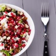 Healthy salad with pomegranate seeds, almond, feta cheese and black rice — Stock Photo #64777127