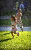 ISTANBUL - JULY 26: Two little girls playing with the automatic irrigation, in July 26, 2014, in Istanbul, Turkey — Stockfoto