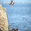 Menorca, Spain - September 8: Young man jumping from cliff into — Stock Photo #56365539