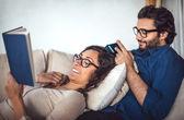 Молодая пара чтение книги на диване у себя дома — Стоковое фото