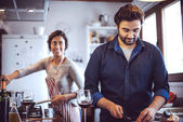 Young couple cooking. Man and woman in their kitchen — Stock Photo