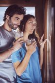 Romantic young couple looking at window — Stock Photo
