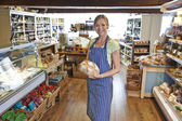 Owner Of Delicatessen Standing In Shop Holding Loaf Of Bread — Photo