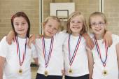 Female School Sports Team In Gym With Medals — Zdjęcie stockowe