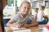 Alumno de la escuela primaria trabajando en mesa de salón de clases — Foto de Stock