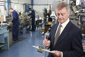 Owner Of Engineering Factory With Staff In Background — Stock Photo