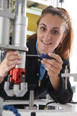 Apprentice Female Engineer Working On Machine In Factory — Stock Photo