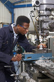 Male Apprentice Engineer Working On Drill In Factory — Stock Photo