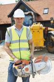 Construction Worker On Site Holding Circular Saw — Stock fotografie